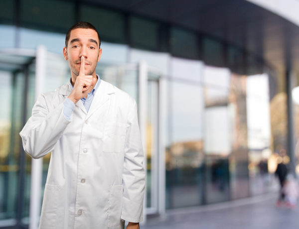 Serious young doctor doing a silence gesture
