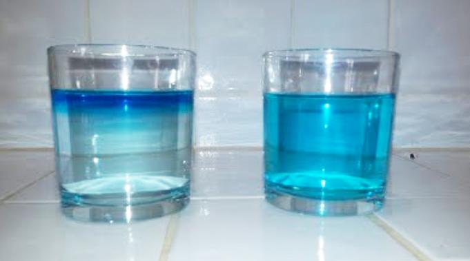Figura 5. Un vaso con agua y sal a la izquierda, y con agua dulce a la derecha. En el caso con sal el agua colorado de fusión del cubito de hielo flota sobre el agua salada.